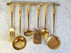 This 7 piece vintage brass hanging utensil set would be very at home in the eclectic rustic kitchen. Comprising of 6 utensils and one hanging rack that can be attached to the wall with screws. Some age marks and tarnishing consistent with material and age, giving them a slightly rustic look. In good vintage condition …