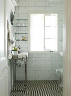 small bathroom with floor to ceiling white tile, all clear glass shower enclosure  and glass shelves for storage