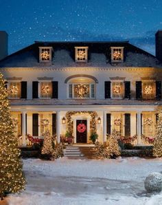 Classic Two Story with Lighted at Night with Christmas Wreaths on Windows Exterior Decorations