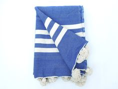 Exotic handwoven Moroccan pom pom blanket made from blue colored handspun wool. This blanket is finished with ivory stripes and pom poms sewn along