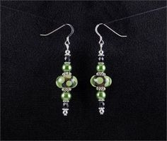 Cute earrings. Green, black, and clear lampwork glass bead polka dot earrings.   *Beads: Lampwork and glass beads   *Earwires: Sterling silver   *All other metal is silver plated.   *Length: 1.75 inches (from the bottom of the earwire)   *Width: 0.6 inches (at the widest part)   *Handcrafted in Fayetteville, Arkansas