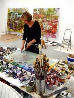 Artist in studio. Painting. Paints spread around palette according to color.