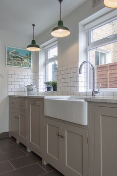 Wide belfast sink, putty units, white worktop. vintage pendant lighting