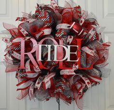 This Alabama wreath is made up of red and silver metallic Deco Mesh that has a bit of sparkle. To make this wreath a lot of fun, there are four different types of ribbon! including a houndstooth tribute to the Bear. And, as if it wasn't already obvious where your allegiance lies, there is a large Roll Tide sign to cheer on the Crimson Tide.