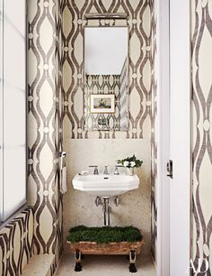 The powder room of a Timothy Whealon-designed home features Dornbracht fittings and Phillip Jeffries wallpaper.