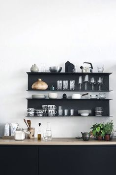 Black metal shelves above black kitchen cabinets. Lovely way to show off the best china.