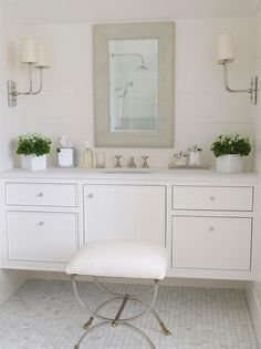 Elegant white bathroom is fitted with Hulton Double Sconces mounted on facing shiplap walls above a white floating washstand adorning small polished nickel knobs, inset cabinets, and a white marble countertop fitted with an oval undermount sink paired with a polished nickel cross handle faucet located beneath a gray vanity mirror as a brass stool sits on gray and white marble grid floor tiles.