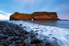 landscape photo of a wave breaking over rocks below hole in the wall, a free standing cliff on south africa's coastline