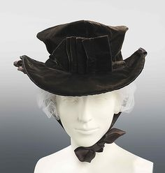 """Hat, 1810-15, American, cotton, silk and jet, """"This shape of hat was worn both with riding habits of the period and as fashionable daywear. The buttons on the sides of the brim of this one probably held cords or ties to keep the hat from flying off during a gallop."""" - in the Metropolitan Museum of Art"""