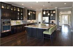 A lighted top row of cabinets and four glass-fronted cabinets that flank the range hood define the Bellingham plan. Built by Standard Pacific Homes at Palencia. Saint Augustine, FL.