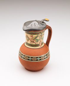 RISD Museum: In the style of Christopher Dresser, Scottish, 1834-1904; Atkin Brothers, silversmith, English, 1853-1925. Jug, ca.1870-1890. Earthenware with enamel and pewter. Height: 17.5 cm (6 7/8 inches) (with closed lid). Gift of Glenn Gissler 2014.17.6