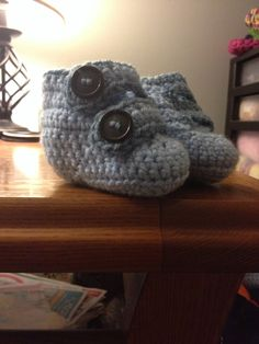Crocheted baby booties with double strap button closure.