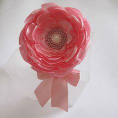 Tiara forrada com fita de cetim, com uma flor de cetim rosa com miolo bordado de vidrilhos e laço rosa.