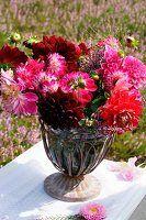 Sommerlicher Blumenstrauss mit Dahlien und Erika auf einem Gartenstuhl