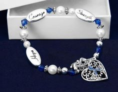 These dark blue ribbon bracelets have dark blue, silver and pearl beads surrounded by 3 silver charms that say Hope Strength and Courage.