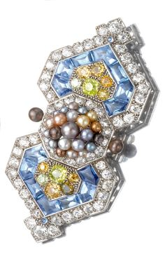 A fine Art Deco gem-set and diamond brooch, Cartier, 1926. The brooch of buckle design set to the centre with a cluster of seed pearls, further set with buff top calibré-cut and cabochon sapphires, circular-cut coloured and colourless diamonds, French assay and partial maker's mark.