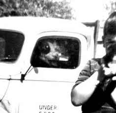 In the photo my brother is holding our kitten with our truck in the background. The problem was we didn't have a dog. None of us recall a white dog in our neighborhood. The strangest part: the dog is transparent, the rear window can be seen through his head. My mother remembers they bought the truck from a rancher who had a sheepdog type of dog. The dog is looking at the boy holding the cat with a great deal of intrest. note the black circle around the dog's eye is the side mirror on the…