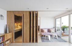Beautiful folding wooden wall divides bedroom and bathroom from the rest of the space.