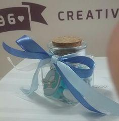 Barattolino vetro base quadra; confetti mandorla sfumati azzurro; doppio nastro raso celeste e azzurro; scarpina decorativa metallo smaltato; battesimo bimbo;