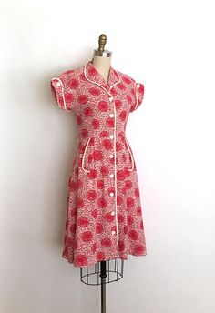 Very lovely 40s shirtwaist day dress. This dress features a fantastic scribble floral print on a grid like background. Classic shirtwaist silhouette, fitted bodice, cute rounded collar and turned up dolmen sleeve cuffs, nipped waist and an a-line skirt with front pockets. Front button closures.