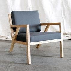 This mid-century styled chair by Gus* Modern features a solid natural oak frame with an interlocking truss base and finger joint detailing on the arms.