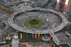 "Circular pedestrian bridge in Lujiazui, China - ""In 2011 year, a new pedestrian bridge was unveiled in Lujiazui in the Pudong district of Shanghai. This large scale circular pedestrian overpass enables pedestrians to avoid traffic at the round-about terminus of Lujiazui Rd....The bridge sits almost 20 feet (6m) above the street, with numerous escalator stairway entrances and exits."""