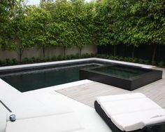 Major pool renovation - added raised 4 side infinity edge spa. Complete re tile in black sheeted pebble and large format black granite on the spa. White concrete pool surround.