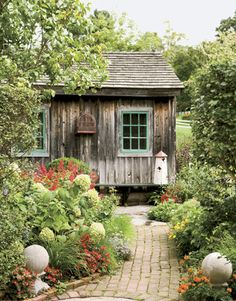 An herb garden thrives outside a former garden shed that serves as a pool house.