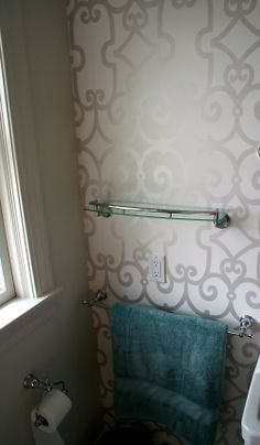 The accent  bathroom wall featuring white wall paper with a silver pattern is a great feature.  The lovely glass shelf trimmed in chrome accessorize the chrome toilet paper holder and towel bars. #RhodeIslandBathroom #RhodeIslandInteriorDesign #Cypressdesignco
