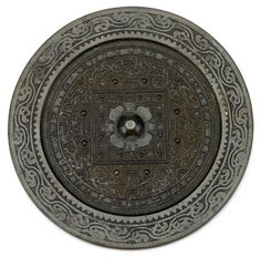 """Chinese bronze mirror     Han     The knob centering a square band of twelve nipples and surrounded by an outer band of eight nipples, archaic and """"TLV designs, between hatchured, sawtooth and wave bands.     D: 7 in."""