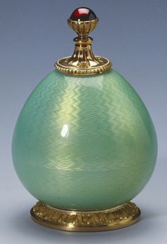 Pear shaped pale green guilloche enamel glue pot with two-colour gold beaded neck mount fitted with brush, the handle of which is fluted gold and set with a cabochon ruby in gold petalled cup. Circular gold foot chased with foliate border.    Mark of Feodor Afanassiev; FABERGÉ in Cyrillic; gold mark of 56 zolotniks and silver mark of 88 zolotniks (1896-1908), circa 1908