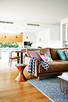 Warm brown leather sofa with great collection of colorful pillows. Plus I spy pale turquoise stools in the background! Love this gorgeous space.