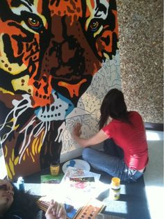 """""""Every spring I give my senior Advanced Placement students the opportunity to create a large scale work of art featuring our high school mascot, a Bengal Tiger. Over the years I have had about a dozen students create a giant acrylic painting which hangs in the large space at the front doors or the high school."""" well, thank you because that is beautiful."""