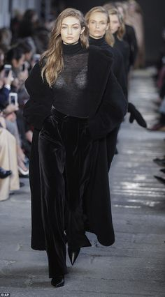 Sheer delight: Gigi Hadid sported a semi see-through black polo neck as she strutted her s...
