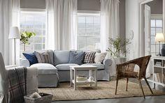 Světlý obývací pokoj se světle modrou dvojmístnou pohovkou a lenoškou. Doplněno malým stolkem a rattanovým křeslem.