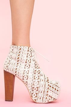 Towering lace-up ivory crochet boots featuring a covered platform and chunky wooden heel. Genuine leather interior, non-slip sole.  By Jeffrey Campbell