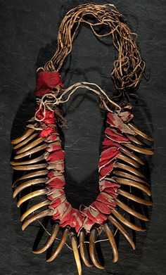 """Cawan's Auctions. This Central Plains Bear Claw Necklace is composed of 29 honey-colored grizzly bear claws connected at the knuckle by hide thongs to otter fur and are strung through the mid-nail by a """"bridle"""" string of sinew; red and beige trade cloth wraps otter fur and separates claws; long thin fringe dotted with quillwork falls at neckline behind necklace, length 17 in.; length of claw 4 in. 19th century."""