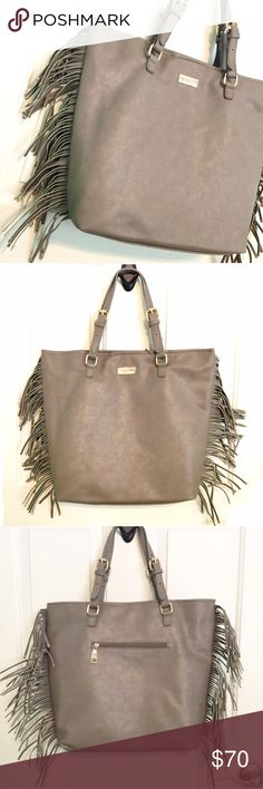 """NWT BCBG Studded Fringe Bag Tote Shopper Taupe An amazing bag with an even better price! This is a NWT BCBG bag in taupe that has studded fringe down both sides. The straps are adjustable so it will suit your comfort needs! Magnetic top closure, 1 zippered pocket on the back, with 1 zippered pocket inside and two slip pockets. Measures approximately 13.5"""" x 16.5"""" x 4"""" with an 8"""" drop. One small mark on lining, might be able to get it out but haven't tried yet! BCBG Bags Totes"""