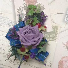 Un ramillete de escocés de señoras con un púrpura espuma rosa hiedra, Hipérico, brezo púrpura, violeta veronica arcos de la cinta de tartán.  Medidas: Longitud: aprox. 5,5 pulgadas Ancho: aprox. 4 pulgadas