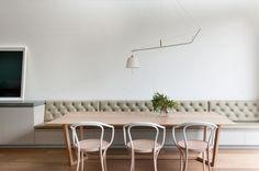 Dining Room Design Ideas - Use Built-In Banquette Seating To Save Space // White walls and lots of natural light help brighten this built-in tufted banquette seating, while a unique light fixture hangs above for extra light on dark days and to brighten evening meals.