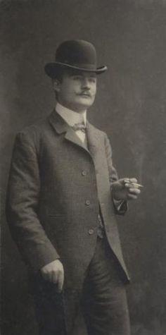 Adriaan Boer | Portretten. Portretfotografie Nederland. Studio-opname, portret van man met bolhoed en snor, sigaret in de ene hand, wandelstok in de andere hand, begin 20e eeuw. [Op de achterzijde staat geschreven Froon?]