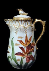 Limoges French porcelain chocolate pot~This fine serving piece has hand painted irises and gold gilt~The pot also has a sea design~The handle is crafted to resemble coral~The top edges have seashell shapes~The lid has a porcelain seashell circa early 1900's