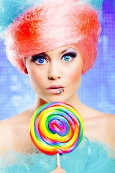Girl with pink & blue hair holding a multicolor swirl lollipop
