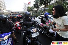 Seorang model dari finalis Abang -None Jakarta, membagikan bunga mawar kepada pengguna motor yang melintas di Bundaran HI Jakarta.