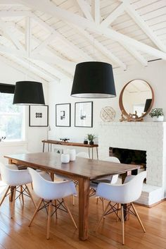 Farm house table, white brick fireplace, round gold mirror, white chairs, black lamp shades