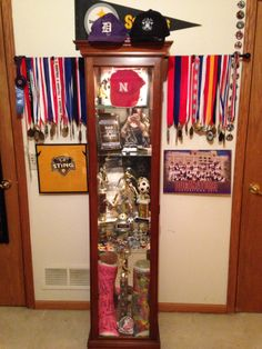How we displayed all of sports medals and trophies/awards....Cheap Curtain Rod from Wal*Mart + Gently Used Curio Caninet from consignment + everything organized and it's place = AWESOMENESS !!  He  L❤️Ves it!!