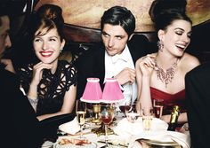 The actress, with Raphaël Personnaz and Josephine de la Baume at Maxim's. On Hathaway, Marchesa red suede strapless dress. Van Cleef & Arpels diamond-and-ruby earrings and necklace, and diamond ring. On de la Baume: ThreeAsFour black corded dress.