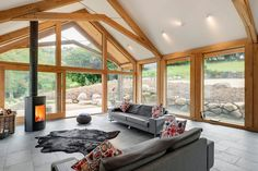 Barn renovation and extension, with green oak and glass extension, riven slate flooring and Scan wood burner stove.