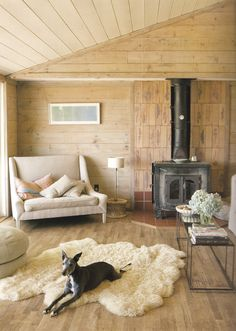 cabin, sheep skin rug, dog, soft blonde wood floors, walls and ceiling from House Beautiful