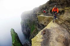 The Cliffs of Moher, Ireland  Mountain bikers ride along the Cliffs of Moher in Ireland, known as one of the most terrifying bike paths in the world.